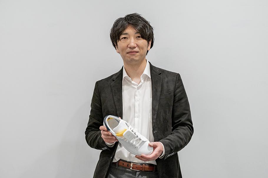 Wataru Chino, Representative Director of Ashirase, Inc. holding a shoe with the Ashirase navigation system