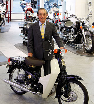 50 years after the first 'The Soba Is Good, Too, Ma!' Super Cub ad, Tsugio Ogata, president of Tokyo Graphic Designers, stands with the 50th anniversary edition of the Super Cub. (2008)